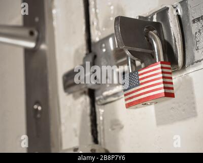 A bolted door secured by a padlock with the national flag of USA on it.(series) - Stock Photo