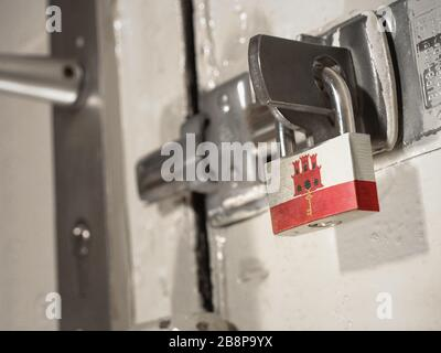 A bolted door secured by a padlock with the national flag of Gibraltar on it.(series) - Stock Photo