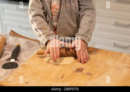 Child girl hands, in white kitchen, flattening pizza dough with a small rolling pin on a wooden board. Lockdown activity idea. - Stock Photo