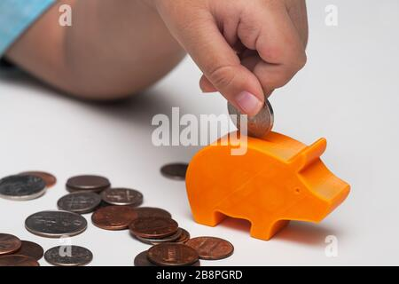 A closeup of a child's hand putting a variety of coins or allowance money into a very small piggy bank. - Stock Photo
