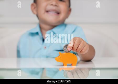 4 year old boy putting a coin into a small piggy bank, using an inferior pincer grasp and showing confidence. - Stock Photo