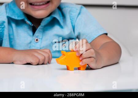 A young boy demonstrating fine motor skills by using a pincer grasp to hold a coin, before putting it into a small piggy bank slot. - Stock Photo