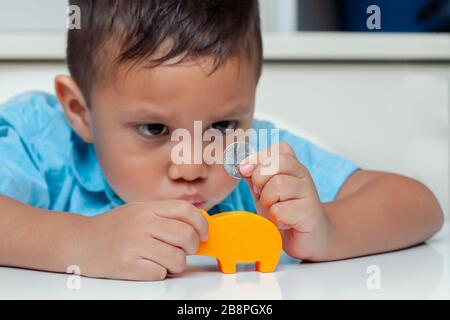 A 4 year old boy starring at a U.S. coin that he is about to put into a small savings piggy bank. - Stock Photo