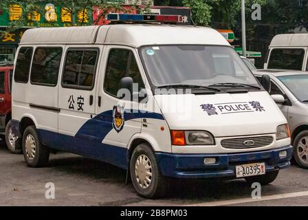 Chongqing, China - May 9, 2010: Downtown. Closeup of white parket Police van with green foliage in back. parts of other cars and yellow mandarin symbo - Stock Photo