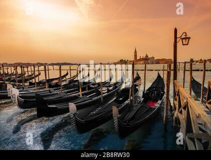 Venice, Italy - March 20, 2020: Gondolas covered with black fabrics stand on the streets of the old city. - Stock Photo