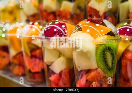 A variety of different colorful fruit salad cocktails at farmers market stall. - Stock Photo