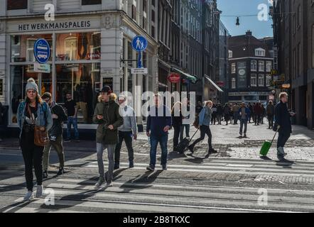 Amsterdam, Holland - Oct 7, 2018. People walking on street in downtown. Amsterdam known for its artistic heritage and narrow houses with gabled facade - Stock Photo