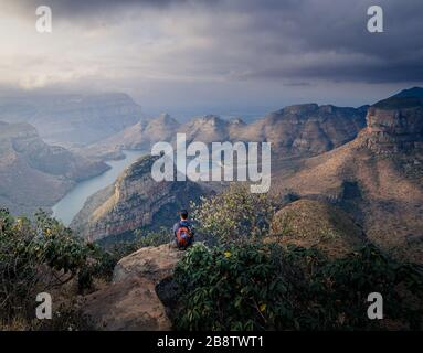 Caucasian man sitting on cliff edge admiring breathtaking view of 3 rondavels from elevated point at Mpumalanga South Africa's panorama scenic route - Stock Photo