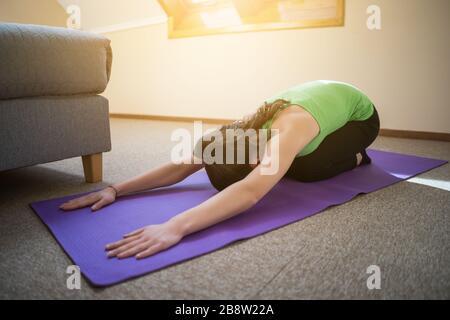 Young woman is practicing yoga at home. Shashankasana / Hare pose - Stock Photo