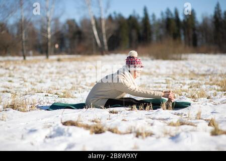 Portrait of gorgeous young woman practicing morning yoga outdoor in city park - Stock Photo