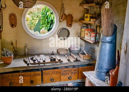 Old rustic potting shed interior, garden view through round window, gardening tools, workbench, retro containers & boxes - York Gate Garden,  Leeds UK - Stock Photo