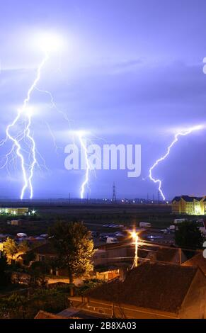 'English: Lightning over the outskirts of Oradea, Romania, during the August 17, 2005 thunderstorm which went on to cause major flash floods over southern Romania. Română: Descărcări elctrice la marginea oraşului Oradea, în timpul furtunilor din 17 august 2005, ce au cauzat de asemenea şi viiturile din sudul României. Technical details: Canon EOS 300D, EF-S 18-55 lens; Exp: 30s; F/13; ISO400; 17 August 2005; Edited version of Image:Lightning over Oradea Romania 2.jpg.; Mircea Madau; ' - Stock Photo
