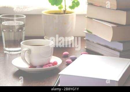 The white paper lies on a wooden table next to a stack of colorful books, a cup of coffee and a pot against - Stock Photo