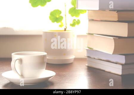 A white cup of coffee stands on a wooden table next to a stack of books and a pot against the background of the window - Stock Photo