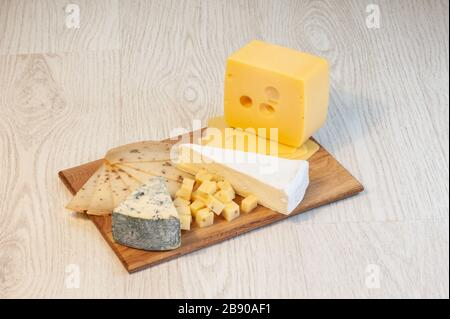 different types of cheese Roquefort cheese, walnut cheese, brie, on a wooden board. - Stock Photo