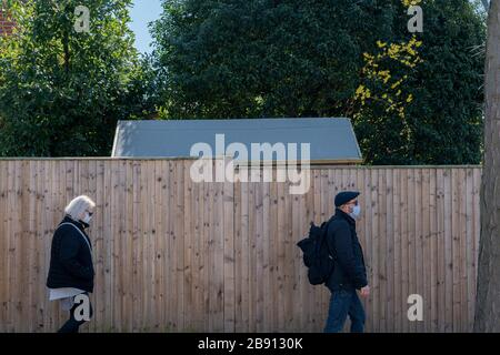 West Dulwich, England, UK. 23rd March 2020. A man and women wearing protective face masks demonstrate social distancing during the Coronavirus Pandemic. London, England. Credit: Sam Mellish / Alamy Live News - Stock Photo