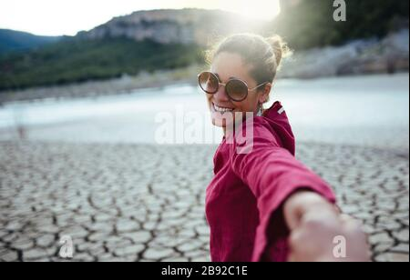 Smiling woman holding her hand for her boyfriend looking at the camera - Stock Photo
