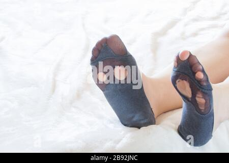 Broken sock with a hole in a female legs. Holes on the heels of the feet. Woman sitting on sofa. Concept of poverty during the crisis - Stock Photo