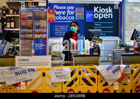 London, UK. 23 Mar, 2020. Coronavirus threat - A Tesco Express lady wearing mask and a barrage between and the customer no touching, keep distance policy on 23 March in Leyton, Tesco, Tesco Express, London, UK. Credit: Picture Capital/Alamy Live News - Stock Photo