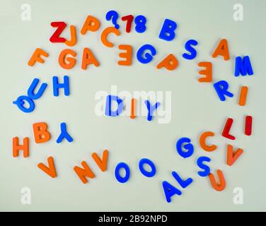 Various different colored letter blocks scattered across an isolated white background - Stock Photo