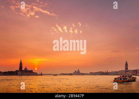 Sunset over Venice, Italy.  Seen is San Giorgio island and the bell tower along with Santa Marie della Salute and St. Mark's Square and the bell tower - Stock Photo