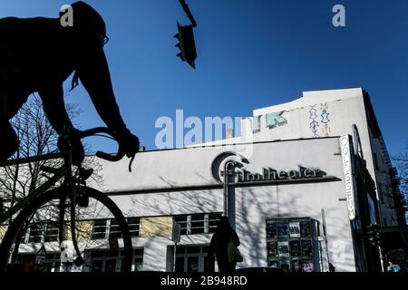 Berlin, Germany. 23rd Mar, 2020. A cyclist waits at a traffic light in front of the closed Collosseum movie theatre in the Prenzlauer Berg district. In order to slow down the spread of the coronavirus, the federal government has considerably restricted public life. Credit: Carsten Koall/dpa/Alamy Live News - Stock Photo