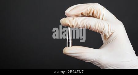 hand in a white disposable glove holding a piercing ear expander for tunnel on a dark background ear jewelry close-up. Stock Photo