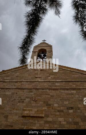 Front wall with bell tower, Greek orthodox basilica of Saint George, Madaba city in Middle East country Kingdom of Jordan. Front yard view with cross and framed by pine tree branch. Cloudy winter day - Stock Photo