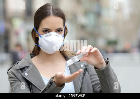 Portrait of a serious woman with protective mask using hand sanitizer looking at camera on street