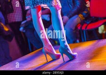 Female model on fashion stage runway legs and heels standing towards public - Stock Photo