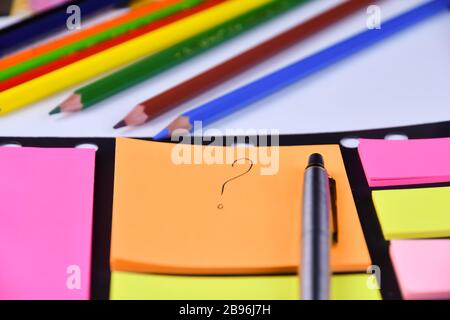 Question mark written by pen on colored stickers on the table, pen and colored pencils lie near - Stock Photo