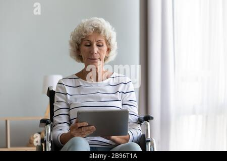 Smart senior disabled woman browsing web on tablet