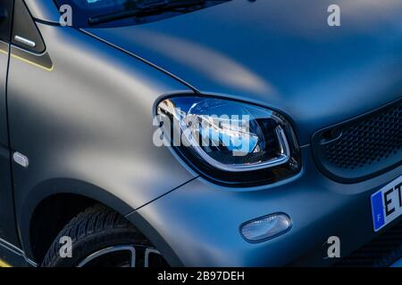 Paris, France - Mar 18, 2020: front view of new LED headlight on the silver MErcedes-Benz Smart car parked on the street