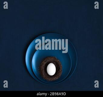 Easter minimalist concept. A chicken egg in a nest on a classic blue background. Copy space, top view, flat lay. - Stock Photo