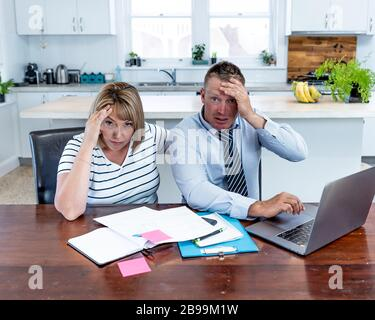 Coronavirus economic recession. Family couple with masks in distress over home finances and small business debts during quarantine and shutdown. impac