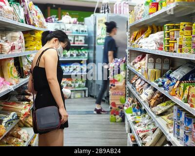 Gold Coast, Australia - March 21, 2020: Asian female wears protective medical mask in asian grocery store amid coronavirus fears, supermarket safety, health hygiene and pandemic concept, covid 19 safe Stock Photo