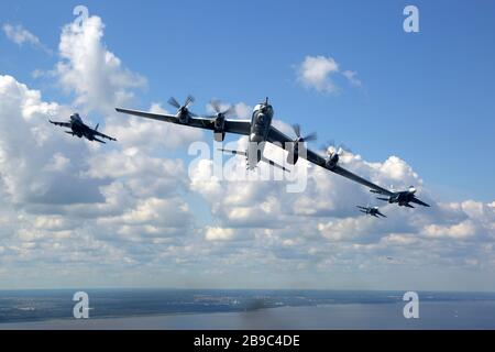 Tu-142MZ airplane in formation with Su-33 jet fighters of the Russian Navy. - Stock Photo