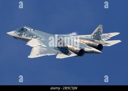 Su-57 jet fighter of the Russian Air Force against a blue sky. - Stock Photo
