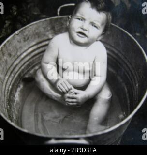 A one-year-old girl is sitting in a tin bathtub. [automated translation]