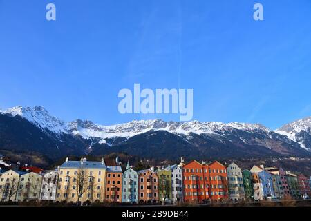 Row of bright colourful houses along the river the Inn in Innsbruck, Austria with majestic mountain peaks covered with snow in the background - Stock Photo
