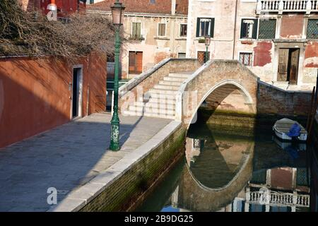 Tranquil residential area along a narrow Venician canal with bridge and with reflection of bridge and building in tranquil water