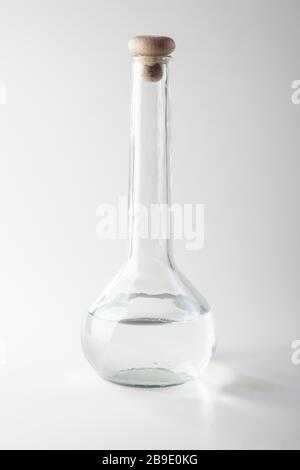 studio shot of bottle with long neck with wooden stopper and clear liquid on light grey background - Stock Photo
