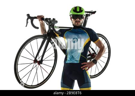 Triathlon male athlete cycle training isolated on white studio background. Caucasian fit triathlete practicing in cycling wearing sports equipment. Concept of healthy lifestyle, sport, action, motion. Stock Photo