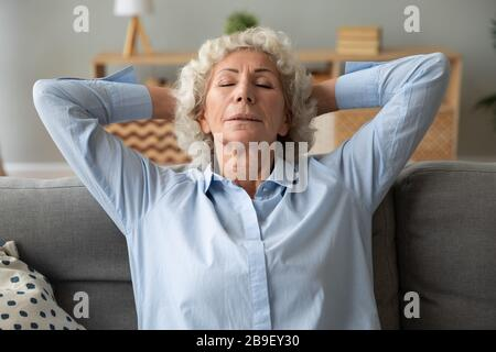 Senior woman relax sleep on cozy sofa at home - Stock Photo