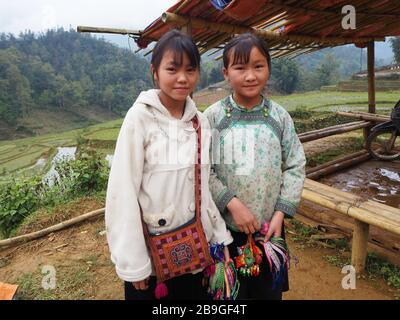 Two young girls selling bracelets to tourists trekking in Sapa, Vietnam - Stock Photo