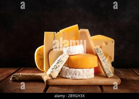 Cheese variety, many different types of cheeses, a side view on a dark background - Stock Photo