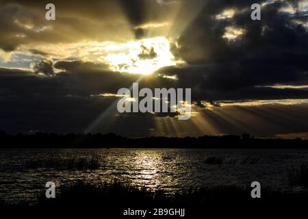 Beautiful sunset landscape with sun rays shining through the clouds - Stock Photo