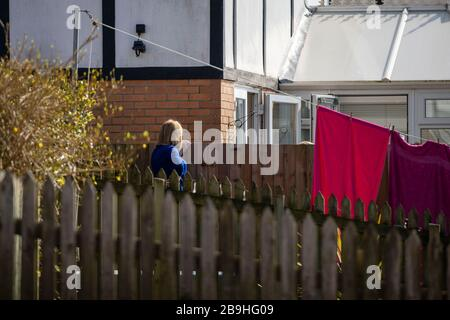 Cardiff, Wales, Uk. 24th Mar, 2020. CARDIFF, WALES, UNITED KINGDOM - MARCH 24, 2020 - Two neighbours chat over a garden fence after strict measures are introduced to keep people at home and slow the spread of coronavirus. Credit: Mark Hawkins/Alamy Live News - Stock Photo