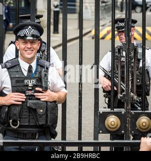 Armed Guards. A friendly London policeman standing guard outside the gates of Downing Street with armed colleagues in the background. - Stock Photo