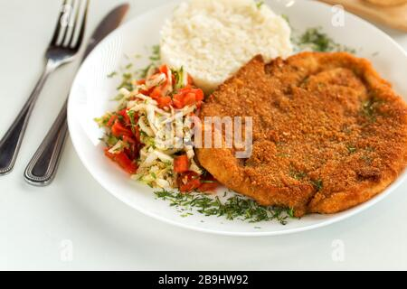 German pork schnitzel with rice and cabbage salad - Stock Photo